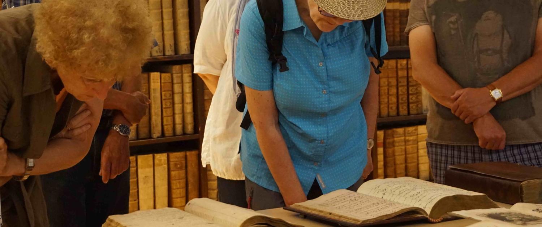 Besucher*innen im Archiv der Uni Salzburg, die einen Blick in die historischen Bücher werfen.